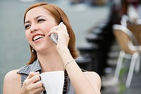 Close_up of a young woman holding a coffee cup and talking on a mobile phone
