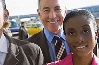 Close_up of a businesswoman with two businessmen smiling