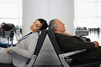 Side profile of a businessman and a businesswoman sleeping on chairs at an airport