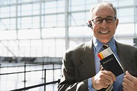 Portrait of a businessman putting a passport with an airplane ticket in his coat's pocket