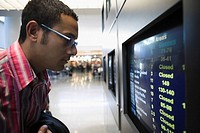 Side profile of a businessman looking at an arrival departure board in an airport