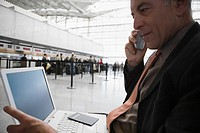 Side profile of a businessman talking on a mobile phone and using a laptop at an airport lounge