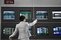 Rear view of a businesswoman pointing at an arrival departure board in an airport