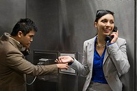 Businesswoman and a businessman talking on pay phones at an airport