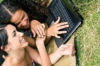 Close_up of female university students working on a laptop and smiling