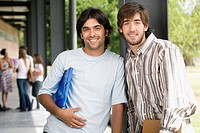 Portrait of two male university students standing in a corridor and smiling
