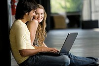 Young woman sitting with a young man working on a laptop