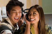 Close_up of a young couple listening to music and smiling