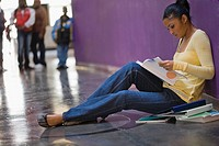 Side profile of a young woman reading a textbook in a corridor (thumbnail)