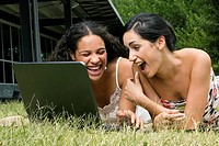 Female university students working on a laptop and laughing
