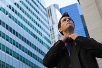 Low angle view of a businessman loosening his tie