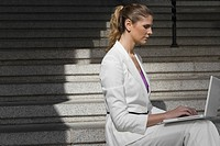 Side profile of a businesswoman sitting on a staircase and using a laptop