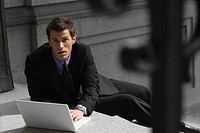 Portrait of a businessman sitting on steps and using a laptop (thumbnail)