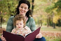 Mid adult woman and her daughter looking at a picture book (thumbnail)