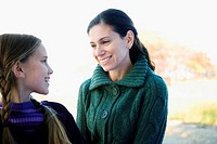 Mid adult woman looking at her daughter and smiling (thumbnail)