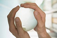 Close_up of a person's hand holding a globe