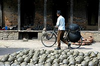 Man with his bycicle and many pots put out for drying on Potters' Square Bhaktapur Nepal