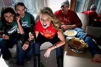 Two young couples sitting on a couch and drinking beer