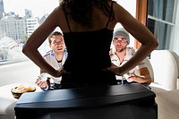 Rear view of a young woman standing in front of a television and two young men looking at her