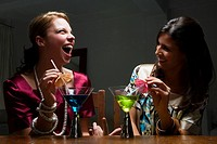 Two young women drinking cocktail and smiling (thumbnail)