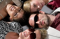 Close_up of a young man with three young women lying down