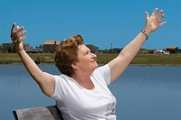 Senior woman sitting at the lakeside with arms outstretched