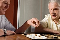Two senior men playing checkers (thumbnail)