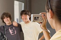 Close_up of a teenage girl taking a photograph of her two friends with a digital camera