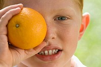 Portrait of a boy holding an orange over his eye