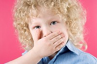 Close_up of a boy covering his mouth with his hands