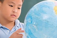 Close_up of a boy looking at a globe