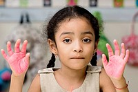 Portrait of a girl showing paint covered hands (thumbnail)