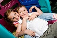 Girl and a boy sitting on a slide and smiling