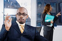 Portrait of a businessman thinking with a businesswoman standing in the background