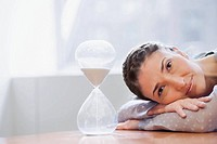 Portrait of a businesswoman resting near an hourglass