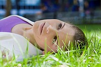 Businesswoman lying on grass in a park