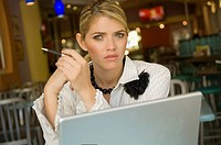 Portrait of a businesswoman sitting in front of a laptop in a restaurant