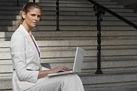 Portrait of a businesswoman sitting on a staircase and using a laptop