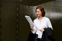 Close_up of a businesswoman reading a newspaper and smiling