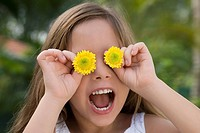 Close_up of a girl holding flowers over her eyes