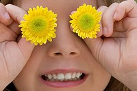 Close_up of a girl covering her eyes with flowers