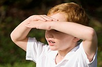 Close_up of a schoolboy shielding his eyes