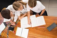 High angle view of two schoolgirls and a schoolboy studying together in a classroom