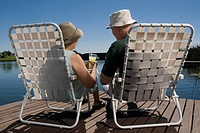 Rear view of a senior couple sitting on chairs at the lakeside
