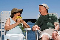 Senior couple sitting at the lakeside and looking at each other