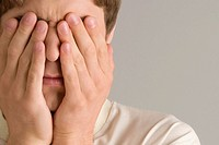 Close_up of a young man covering his eyes with his hands