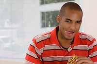 Portrait of a young man eating a sandwich