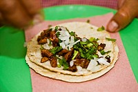 Close_up of a person's fingers preparing Mexican taco, Cuetzalan, Puebla State, Mexico