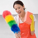 Young woman holding a duster and a bath sponge