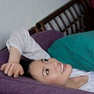 Young woman lying on a couch and smiling (thumbnail)